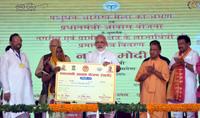 The Prime Minister, Shri Narendra Modi distributing the certificate to beneficiaries of the Pradhan Mantri Awas Yojana (Rural & Urban), at Shahanshahpur, Varanasi, Uttar Pradesh on September 23, 2017. The Governor of Uttar Pradesh, Shri Ram Naik and the Chief Minister, Uttar Pradesh, Yogi Adityanath are also seen.